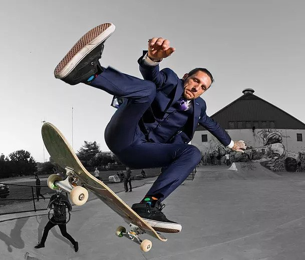 Brandon Novak skateboarding in a blue suit and black sneakers